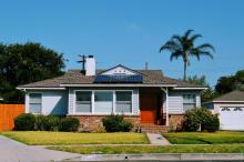 Solar panels on roof of blue cottage in Los Angeles, CA
