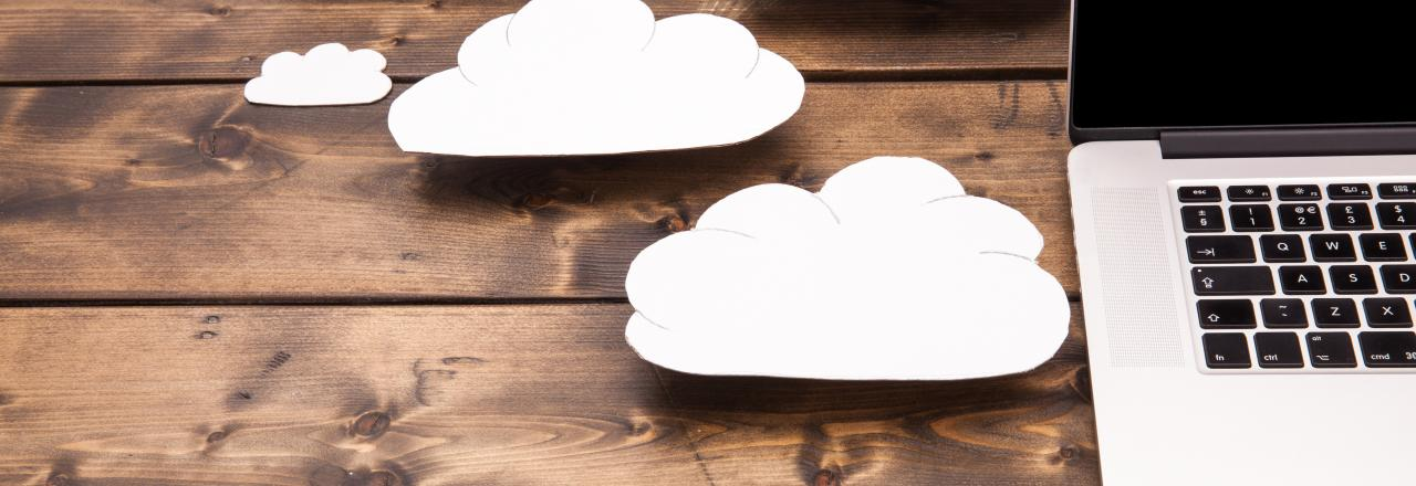 Laptop on Wooden Background with Paper Clouds
