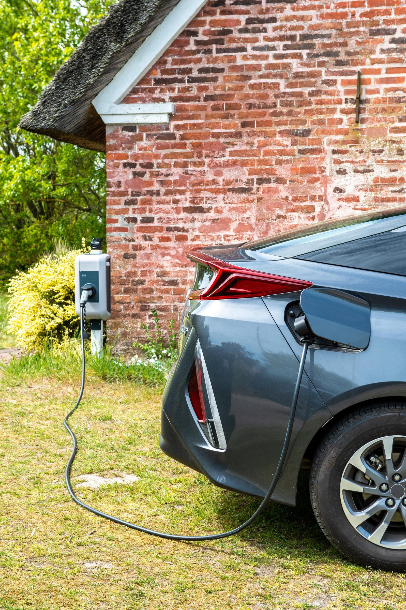 electric car charging in front of brick home