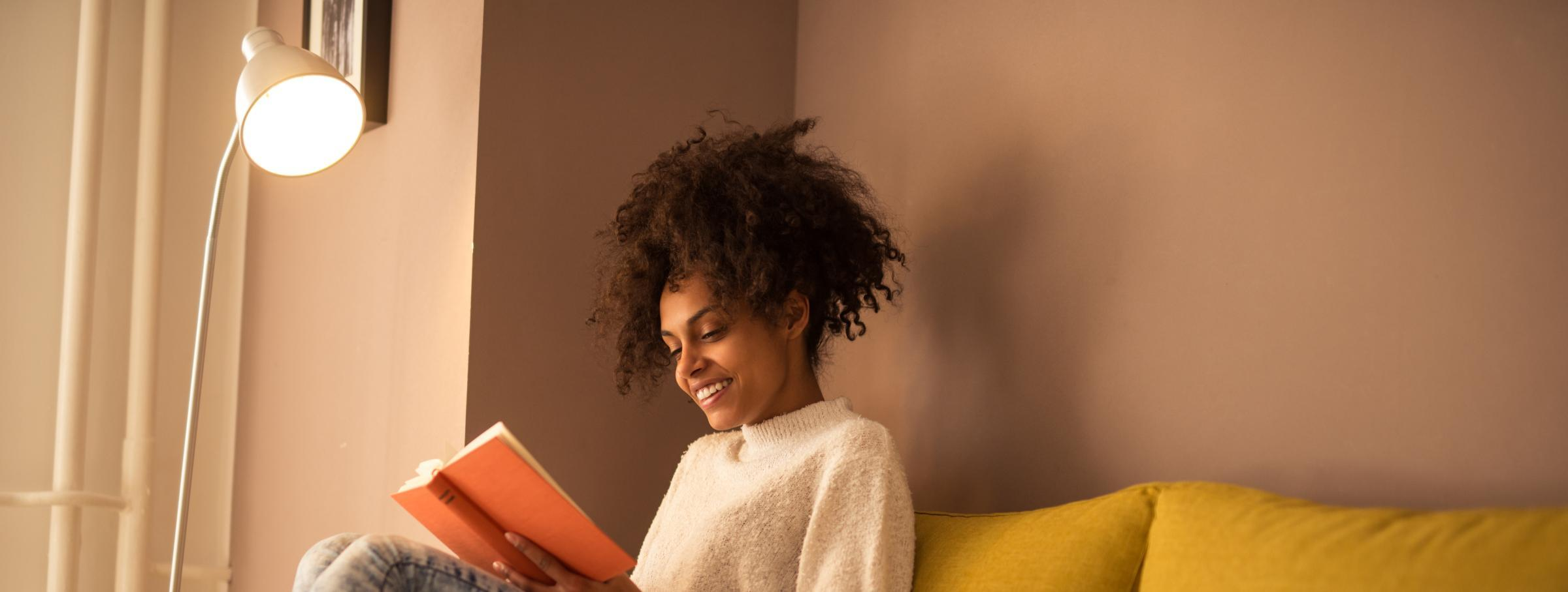Woman reading a book under a lamp