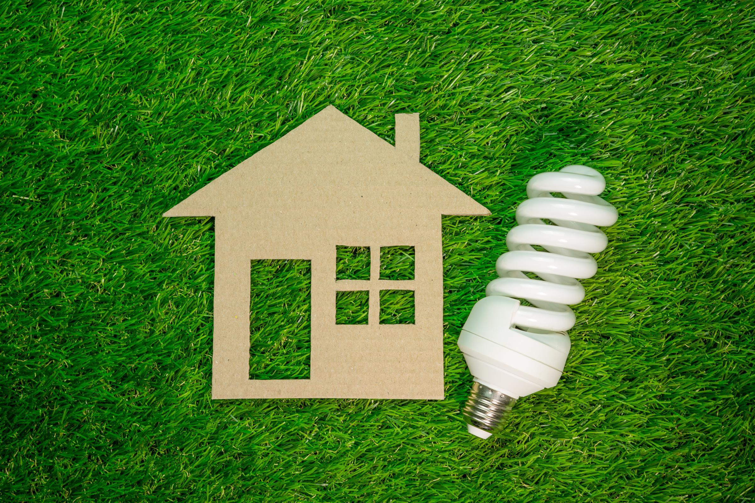 Cut-out paper home next to a CFL light bulb on a grass background